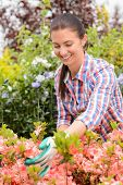Garden center woman worker looking down at pink flowerbed smiling