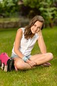 Smiling teenage girl sitting on grass with pink satchel summer