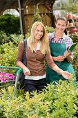 Garden center worker and woman customer shopping for plants smiling