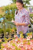 Garden center woman write inventory notes by potted flowers