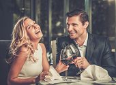 image of cheer  - Cheerful couple in a restaurant with glasses of red wine - JPG