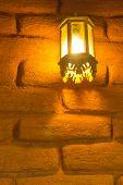 Lamp With A Brick Wall Made Of Orange Bricks.