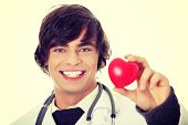 Happy handsome young male doctor holding heart shape toy
