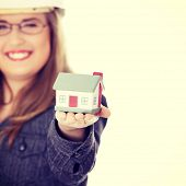 Young beautiful business woman with house model - real estate concept.