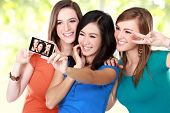 picture of selfie  - Three multi racial young girl friends taking a picture of themselves on a smart phone - JPG