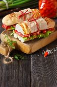 foto of sweetie  - Salami sandwiches with lettuce and sweety drop peppers on an old wooden board with place for text - JPG