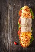 image of sweetie  - Salami sandwich with lettuce and sweety drop peppers on an oldwooden board with place for text - JPG