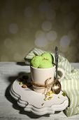 Tasty pistachio ice cream in cup on wooden table, on light background