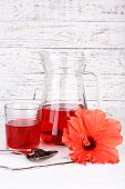picture of hibiscus  - Cold hibiscus tea in glass jug with hibiscus flower on wooden background - JPG