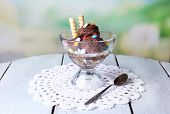 Chocolate ice cream with multicolor candies and wafer rolls in glass bowl, on color wooden table, on bright background