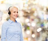 business and office concept - friendly female helpline operator with headphones