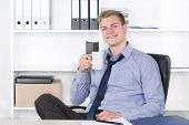 Young Smiling Man Is Drinking A Cup Of Coffee In The Office