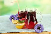 Red basil lemonade in jug and glass, on wooden table, on bright background