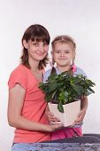 Mom And Daughter With A Potted Flower In Hands