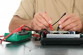 a person uses a voltage meter to check for dead circuits, faults and shorts in an electronic device.