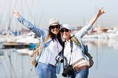 happy female tourists enjoying their vacation by the harbor
