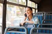 image of commutator  - beautiful female commuter talking on cell phone while taking bus to work - JPG