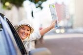 beautiful female tourist traveling in a car waving a map