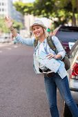 image of hail  - pretty tourist hailing a cab in the street  - JPG