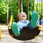 image of swing  - Happy little blond boy having fun on a swing in a summer park - JPG