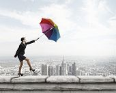 Young businesswoman walking on roof with colorful umbrella