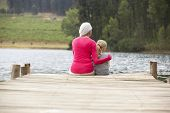 Grandmother and granddaughter sitting on a jetty
