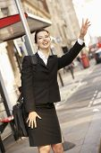 Businesswoman hailing bus at stop
