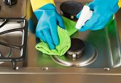 Gloved Hands Cleaning Stove Top Range With Spray Bottle And Microfiber Rag