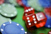 stock photo of gambler  - casino chips and dices stacking on a green felt - JPG