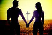 Atmospheric conceptual image of the silhouettes of a romantic young couple holding hands standing wi