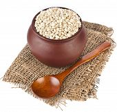 pearl barley porridge  in a clay pot with a spoon   isolated on white background