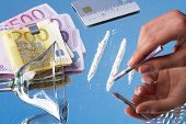 stock photo of drug addict  - 2 lines of cocaine and banknotes on blue background - JPG