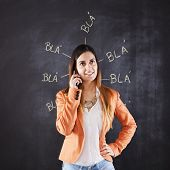 Woman speaking at her cellphone next to a chalkboard