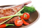 meat food : grilled beef spare rib on dark dish with thyme pepper and tomato isolated over white bac
