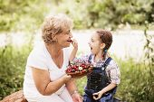 stock photo of child feeding  - granddaughter is feeding her grandmother with cherries in the garden - JPG