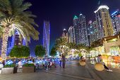 DUBAI, UAE - 31 MARCH 2014: Promenade in Dubai Marina at night, UAE. Dubai Marina is a district in Dubai with artificial canal city who accommodates more than 120,000 people at Persian Gulf.