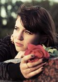 Sad young woman with a red rose
