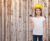 construction and people concept - smiling little girl in protective helmet with paint brush