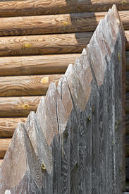 stock photo of stockade  - Fragment of old palisade on the background of a timbered wall - JPG