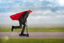 stock photo of hair motion  - senior superhero man riding a scooter with cape and mask - JPG