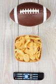 Getting ready to watch a Bowl Game. High angle shot of an American football, a bowl of potato chips and a TV remote on a white wood table. Vertical format