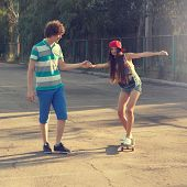 Teen Boy Helping Teen Girl To Ride A Skateboard