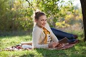 woman lying on bedding on green grass with tablet during rest in the park