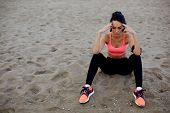 Exhausted female runner resting after workout sitting on beach