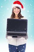 Smiling brunette in santa hat showing her laptop against blue vignette