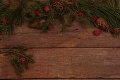fur-tree both pine branches and cones and decorative red apples on a wooden table