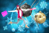 Happy brunette jumping with gifts bags against hanging christmas decorations