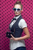 Fashionable Teen Girl With Vintage Camera In Blue Sunglasses On Dotted Pink Background