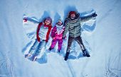 Young couple and cute little girl having fun in snowdrift