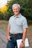 Happy Emotional Old Man Smiling. Posing In The Park. Outdoor. Blue Jeans. Grey T-shirt. Watch